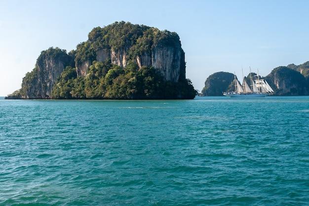 Een grote rots in de turquoise zee en een witte zeilboot vlakbij