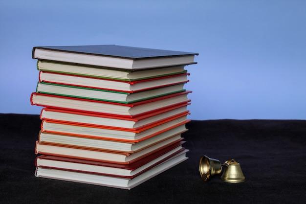 Een grote stapel boeken en een bel zijaanzicht op een blauwe achtergrond