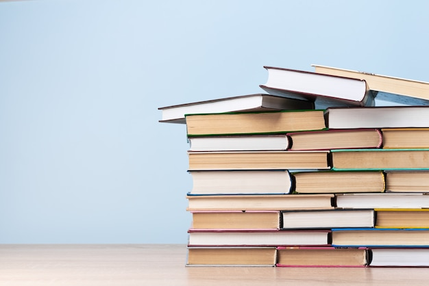 Een grote stapel boeken staat op een houten tafel tegen een lichtblauwe muur