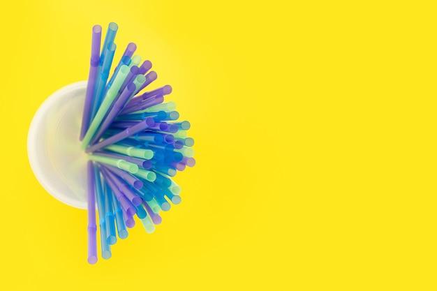 Een grote stapel kleurrijke plastic rietjes waaierde uit in een glas