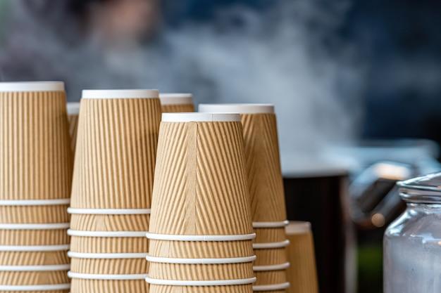 Een grote stapel papieren bekers naast een koffiemachine in een straatcafé op een kerstmarkt