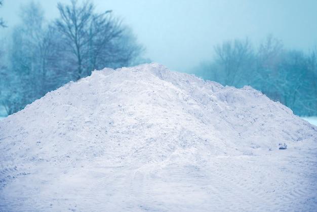 Een grote stapel sneeuw in de straat in de buurt van de weg, winterseizoen