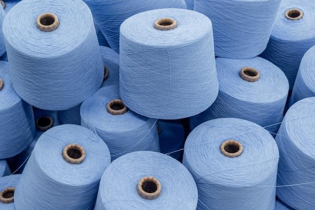 Een grote stapel spoelen van blauwe draad. detailopname