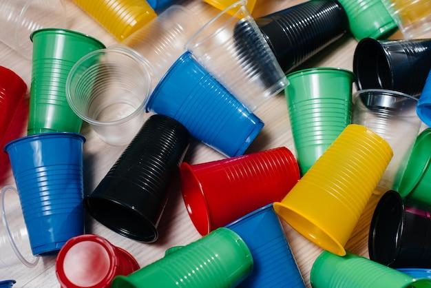 Een grote stapel veelkleurige plastic bekers verspreid over de vloer. vervuiling van het milieu door menselijk afval.