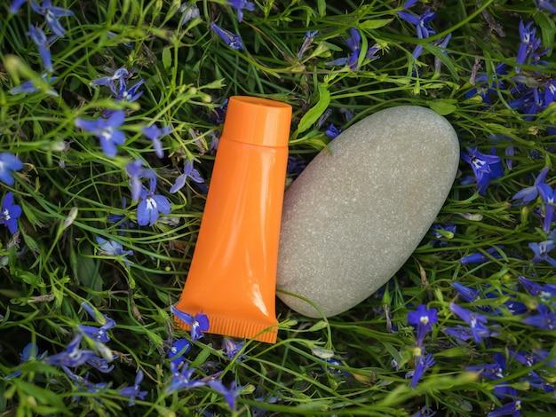 Een grote steen en een oranje tube crème op een achtergrond van bloemen.