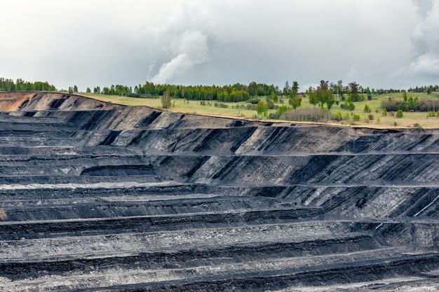 Een grote steengroeve met vele horizonten en richels. verticale bedding van steenkoollagen.