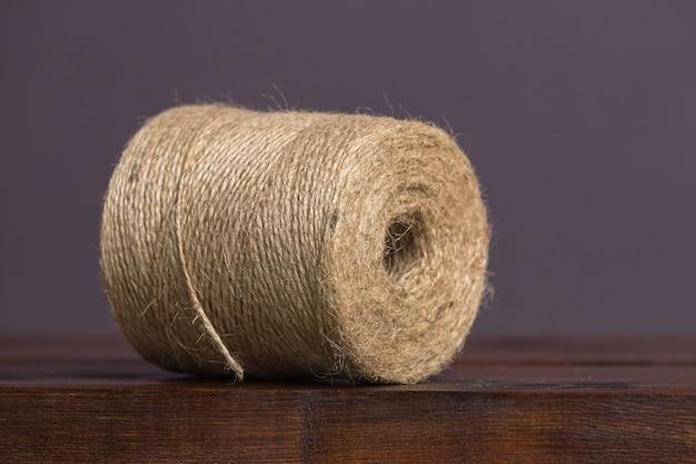 Een grote streng bruin touw ligt op een houten plank op een effen achtergrond