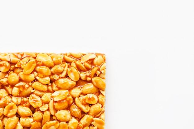Een grote tegel van geroosterde pinda'sreep in zoete melasse. kozinaki nuttige en smakelijke zoetigheden van het oosten