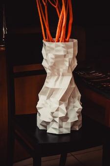 Een grote vaas gedrukt op een 3d-printer staat op een stoel in een interieurclose-up