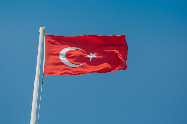 Een grote vlag van turkije in de wind tegen de blauwe lucht