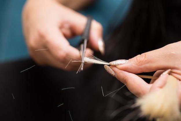 Een haarlok voorbereiden op verlenging. haar en haarhulpmiddelenclose-up.