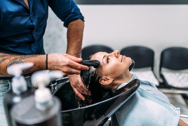 Een haarwassing krijgen in de schoonheidssalon. ontspannen gezicht van vrouwelijke cliënt op badkamersgootsteen.