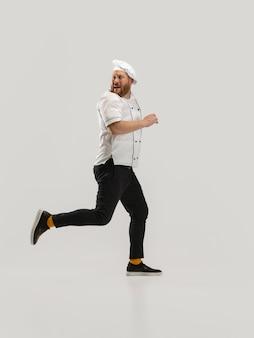 Een had een bebaarde man, kok, mannelijke chef-kok in wit uniform gesneden komkommer springen geïsoleerd op wit