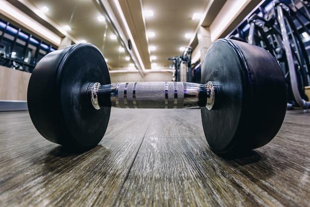 Een halter in de sportschool op de vloer met een fisheye-lens, dramatisch gymschot