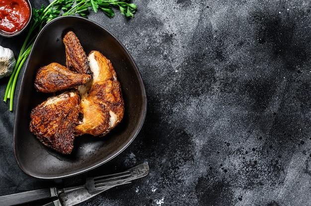 Een halve gegrilde kip op een bord. zwarte achtergrond