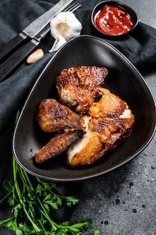 Een halve gegrilde kip op een bord