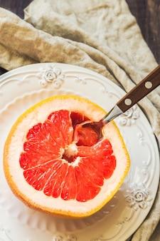 Een halve grapefruit op vintage bord met lepel op rustieke houten achtergrond. gezond ontbijt.