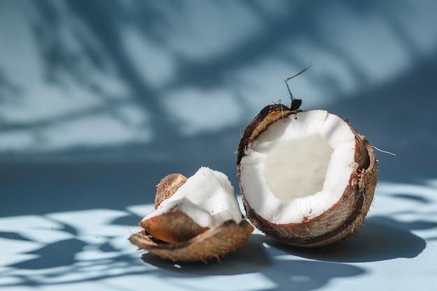 Een halve kokosnoot en stukjes kokos op een blauwe achtergrond.