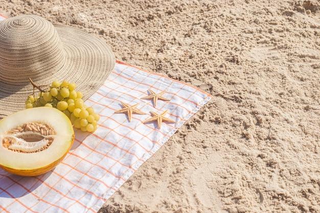 Een halve meloen, druiven, zeester op het strand. bovenaanzicht, plat gelegd.