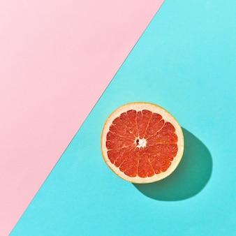Een halve rijpe grapefruit op een dubbele roze en blauwe kartonnen achtergrond met ruimte voor tekst. citrusvrucht. bovenaanzicht