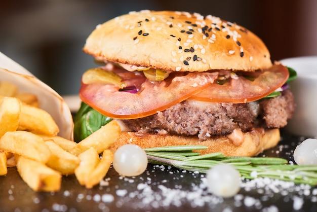 Een hamburger bestaande uit vleespasteitjes, kaas en groenten geserveerd op een stenen bord close-up