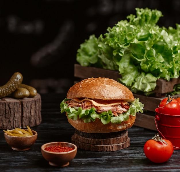 Een hamburger geserveerd met turshu en sumakh op een rustieke tafel