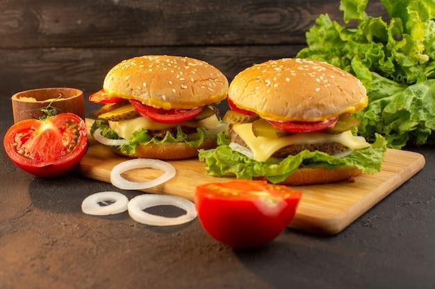 Een hamburger van de vooraanzichtkip met kaas en groene salade op het houten bureau en de groenten van de sandwich fastfoodmaaltijd