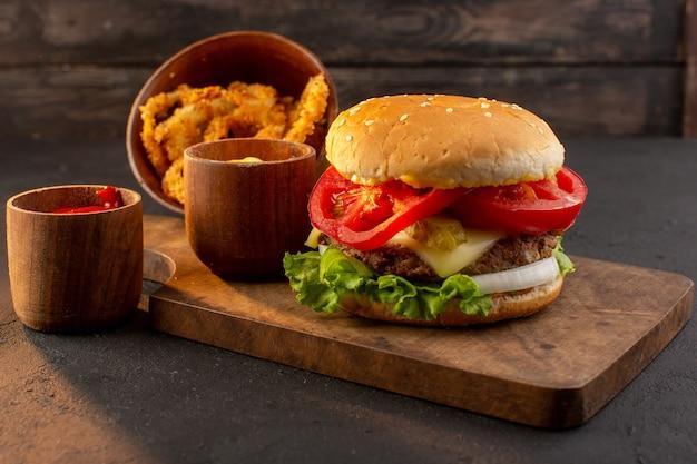 Een hamburger van de vooraanzichtkip met kaas en groene salade op het houten bureau en sandwich fastfoodmaaltijd