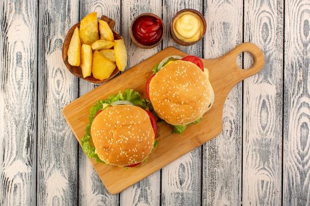 Een hamburger van het bovenaanzicht vlees met kaas en groene salade aardappelen en dipsauzen