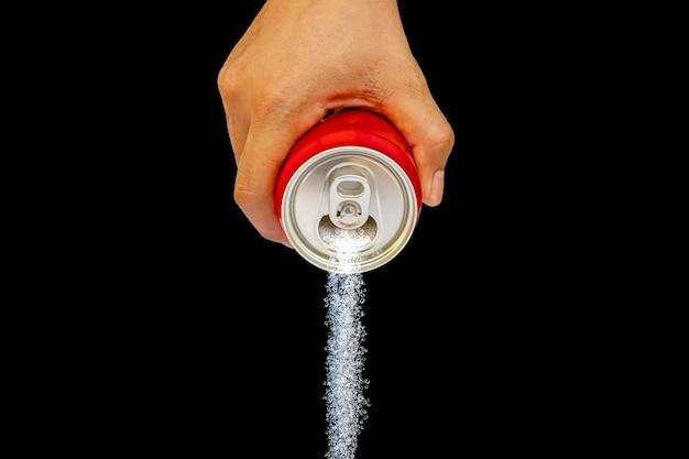 Een hand die een drankblikje vasthoudt en grote hoeveelheden suiker giet, geïsoleerd op een zwarte achtergrond, concept om het suikergehalte van een verfrissend drankje te vergelijken.