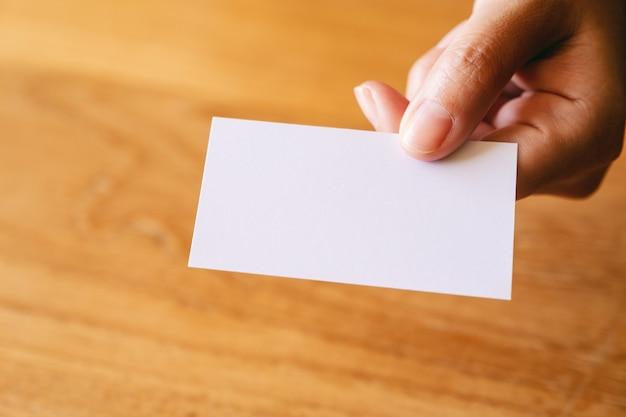 Een hand die een leeg visitekaartje vasthoudt en geeft