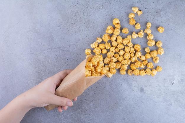 Een hand die een pak met karamel gecoate popcorn op een marmeren oppervlak morst