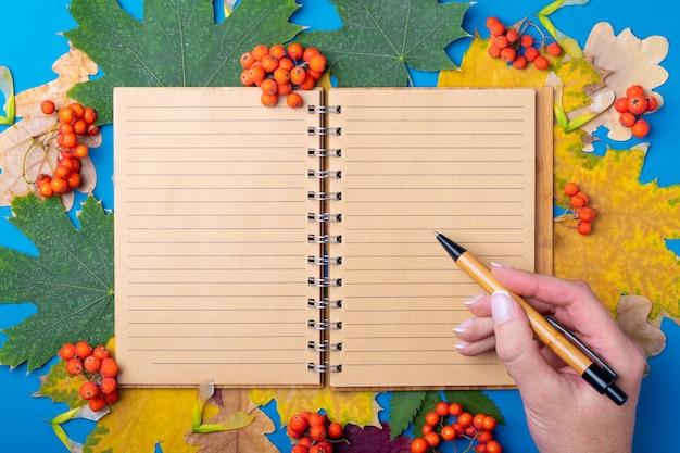 Een hand die een pen vasthoudt boven een blanco beklede ambachtelijke notitieblok op een achtergrond van herfst gevallen droge kleurrijke bladeren. studeer op school in de herfst in het concept van september en oktober. terug naar schoolconcept.