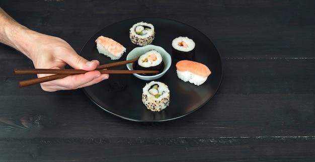 Een hand die een sushirol in saus dompelt