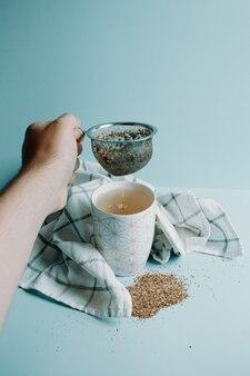 Een hand die een theedistilleerder grijpt bij een kopje thee op een pastelblauwe achtergrond