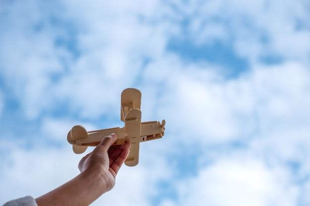 Een hand die en een houten vliegtuig houdt in blauwe hemelachtergrond stijgt