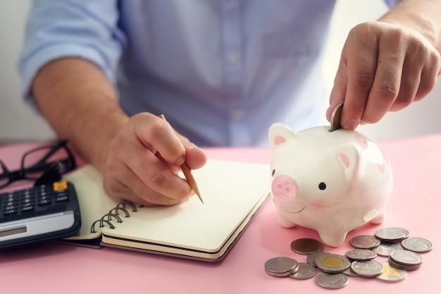 Een hand die geldmuntstuk zet in spaarvarken. een besparing voor toekomstig investeringsconcept.
