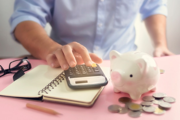Een hand die op calculatorclose-up voor uitgavenlijst tellen met geldmuntstuk en spaarvarken. een besparing voor toekomstig investeringsconcept.