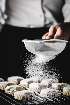 Een hand die suikerpoeder op smakelijke traditionele kavala-koekjes strooit