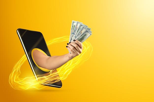 Een hand die via een smartphone naar buiten komt, houdt geld vast