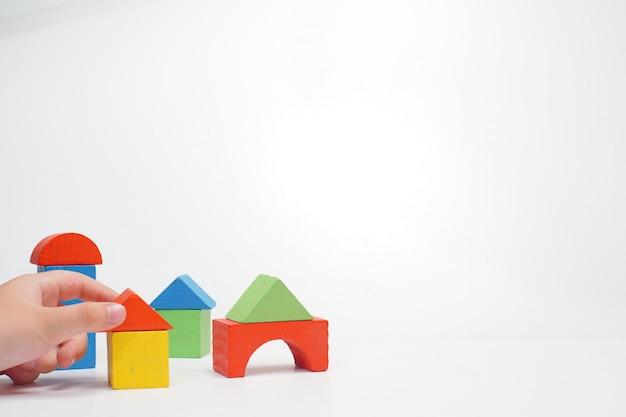 Een hand en houten gekleurde stuk speelgoed blokken op wit.