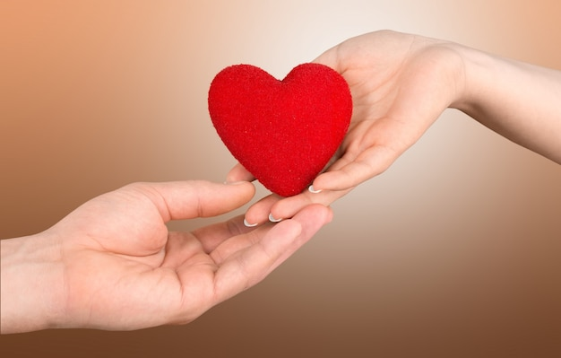 Een hand geeft een rood hart aan een hand - bloeddonatie, wereldbloeddonordag