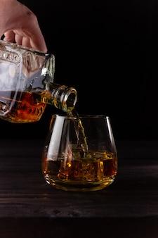 Een hand giet cognac uit een karaf in een glas. alcoholische dranken