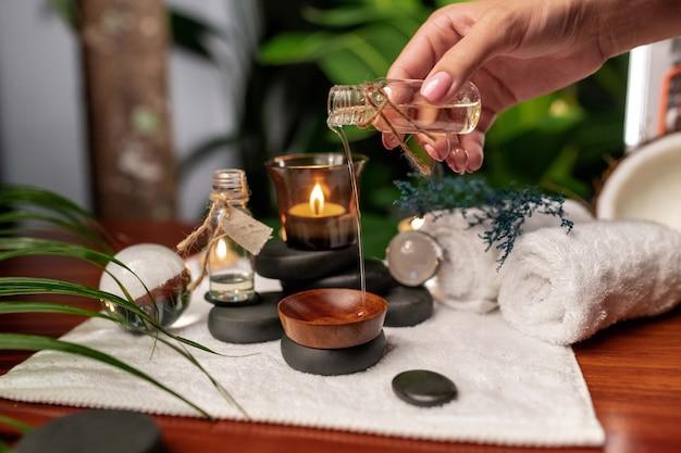 Een hand giet olie uit een pot aromatische oliën die op stenen staan voor steentherapie en zich op een badstofhanddoek bevinden