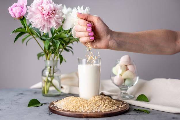 Een hand giet rijstkorrels in een glas natuurlijke rijstmelk op tafel