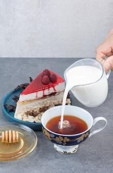 Een hand gieten melk in kopje koffie op grijze tafel.