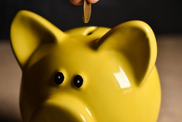 Een hand gooit een munt in een geel spaarvarken