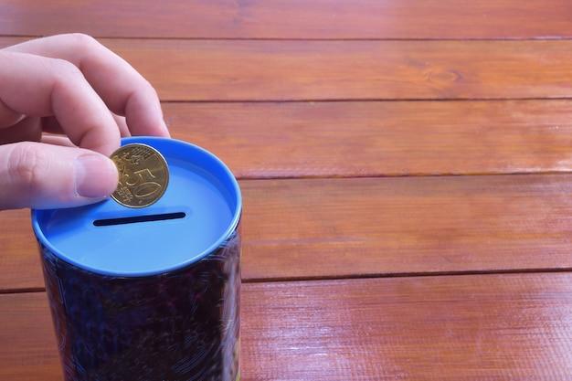 Een hand houdt 50 eurocent vast boven een spaarvarken op een houten ondergrond aan de rechterkant is een plaats
