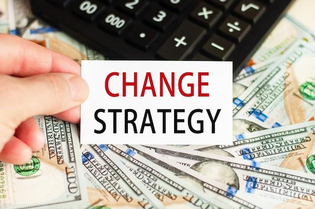 Een hand houdt een bord vast met de inscriptie - verander strategie op de achtergrond van bankbiljetten en een rekenmachine op tafel.