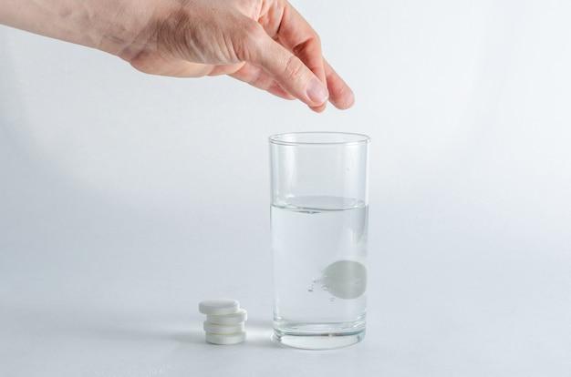 Een hand houdt een bruisende, oplosbare tablet vast en plaatst deze in een glas water.
